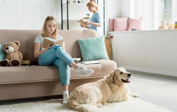 Teen sitting on a couch reading a book.