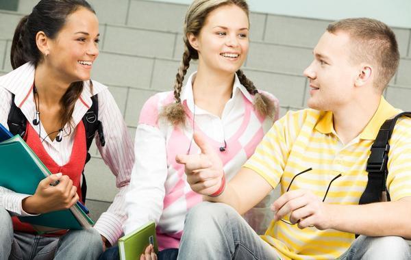 Three teenagers sitting and talking.