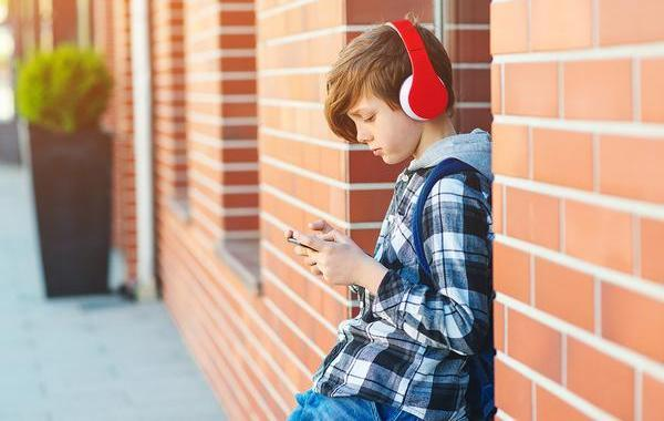 Young teen leaning against a brick building looking at his phone.